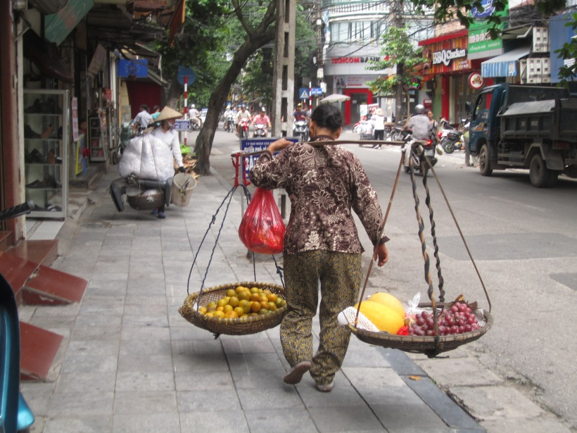 A woman carrying her wares in Hanoi, Vietnam.