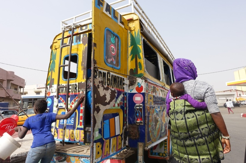 Women, baby and teenage exiting a colorful, crowded bus.